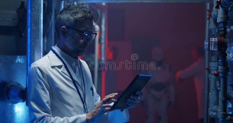 Επιστήμονας που ελέγχει τον εξοπλισμό και που χρησιμοποιεί την ταμπλέτα στοκ φωτογραφία με δικαίωμα ελεύθερης χρήσης