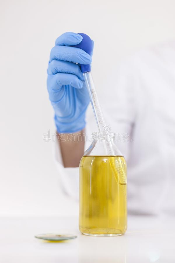 Επιστήμονας που εργάζεται με το φαρμακευτικό πετρέλαιο cbd σε ένα εργαστήριο με dropper γυαλιού και ένα κύπελλο στοκ εικόνες