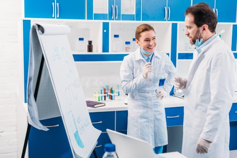 επιστήμονας στα άσπρα παλτά κοντά στον πίνακα για τις σημειώσεις που διοργανώνουν τη συζήτηση κατά τη διάρκεια της εργασίας στοκ εικόνες