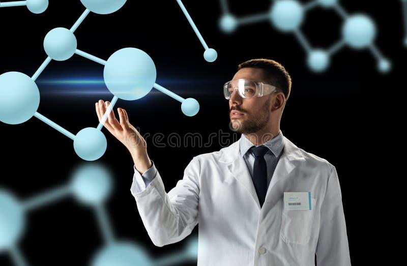 Επιστήμονας στο παλτό εργαστηρίων και προστατευτικά δίοπτρα με τα μόρια στοκ εικόνες