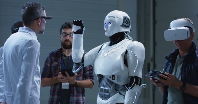 Επιστήμονες που εξετάζουν τις χειρονομίες ρομπότ στοκ εικόνες