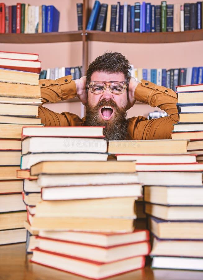 Επιστημονική έννοια ανακαλύψεων Ο δάσκαλος ή ο σπουδαστής με τη γενειάδα φορά eyeglasses, κάθεται στον πίνακα με τα βιβλία, άτομο στοκ φωτογραφίες