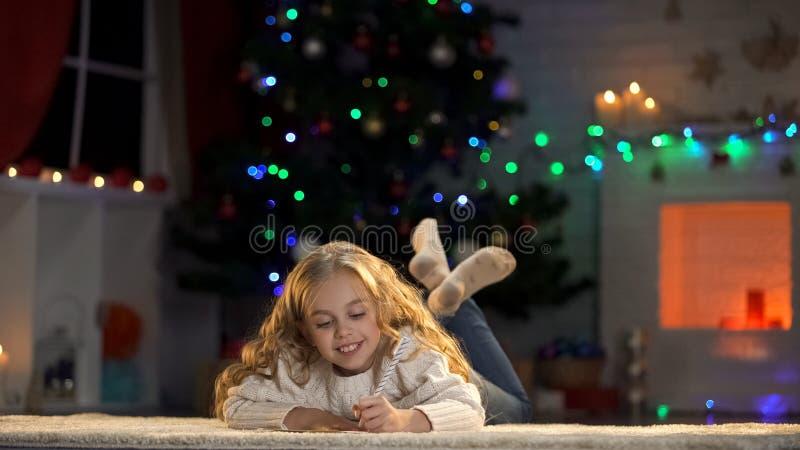 Επιστολή γραψίματος μικρών κοριτσιών σε Santa που βρίσκεται στο πάτωμα, πεποίθηση στο μαγικό παραμύθι στοκ εικόνες με δικαίωμα ελεύθερης χρήσης