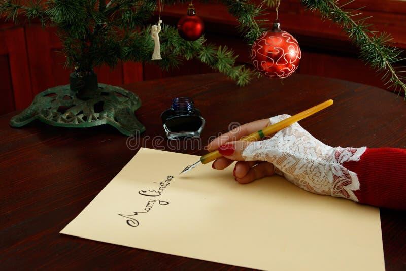 Επιστολή Χριστουγέννων γυναικείου γραψίματος στον ξύλινο πίνακα στοκ εικόνες με δικαίωμα ελεύθερης χρήσης
