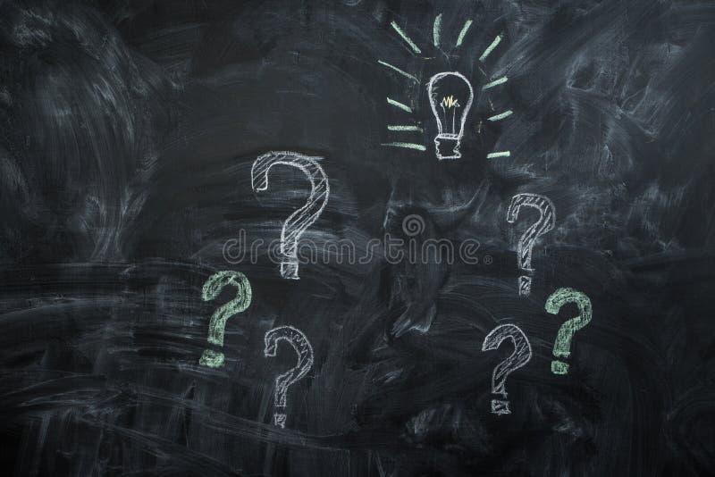 Επισυμένος την προσοχή στα μαύρες ερωτηματικά και τη λάμπα φωτός πινάκων κιμωλίας στοκ εικόνες με δικαίωμα ελεύθερης χρήσης