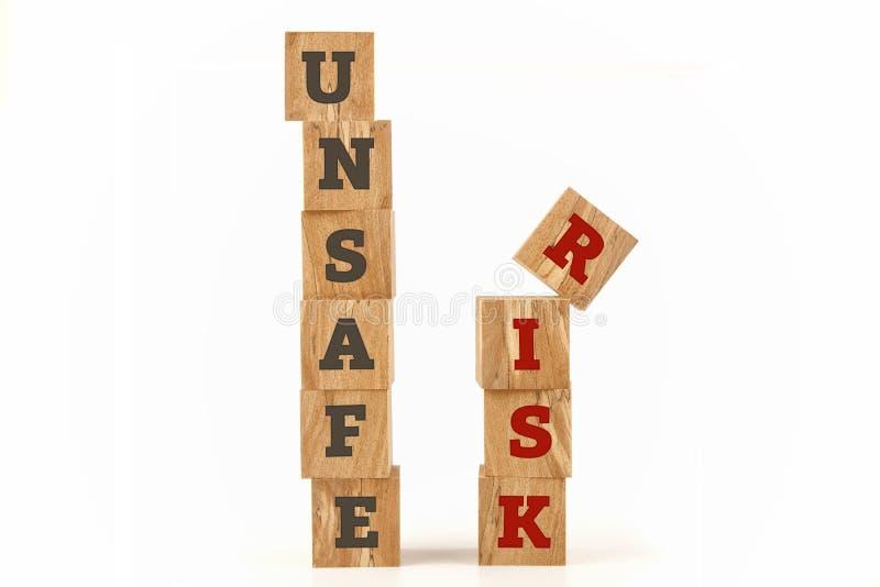 Επισφαλής και λέξη κινδύνου που γράφεται στη μορφή κύβων στοκ φωτογραφία