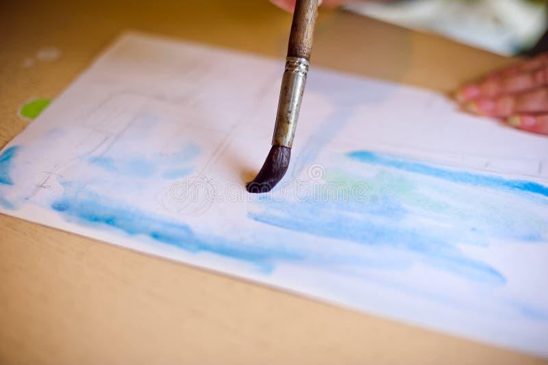 Επισύρει την προσοχή τη βούρτσα στο μπλε εγγράφου στοκ φωτογραφίες
