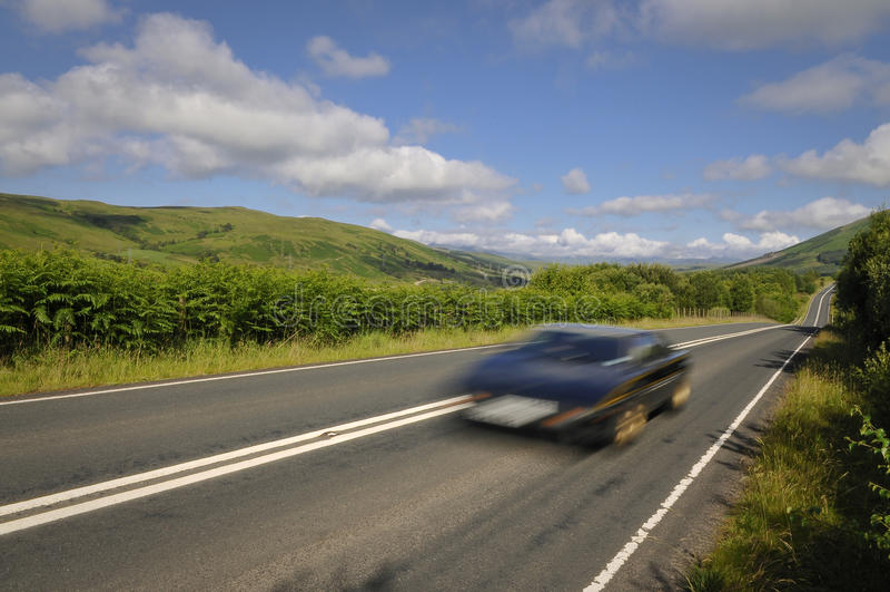 Επιταχυνόμενο αθλητικό αυτοκίνητο στο δρόμο βουνών στοκ φωτογραφίες
