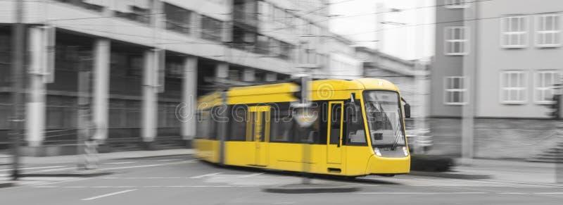 επιταχυνόμενο κίτρινο τραμ με το γραπτό υπόβαθρο πόλεων στοκ φωτογραφία με δικαίωμα ελεύθερης χρήσης