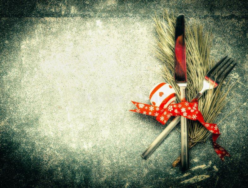 Επιτραπέζια θέση Χριστουγέννων που θέτει με τα μαχαιροπήρουνα, τους κλάδους πεύκων και τη διακόσμηση στο σκοτεινό αγροτικό εκλεκτ στοκ φωτογραφίες με δικαίωμα ελεύθερης χρήσης