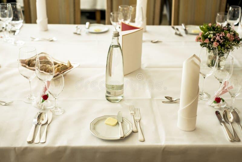 Επιτραπέζια οργάνωση στο γάμο που περιμένει τους φιλοξενουμένους με τα λουλούδια νερού πιάτων στοκ φωτογραφίες