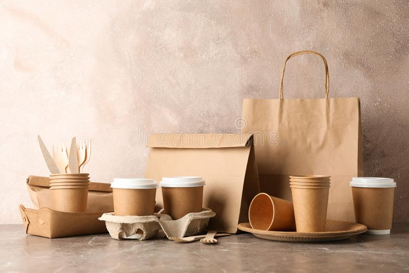 Επιτραπέζια σκεύη φιλικά προς το περιβάλλον και χάρτινη σακούλα σε γκρι τραπέζι στοκ εικόνες