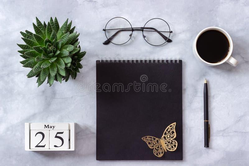 Επιτραπέζιο γραφείο γραφείων ή σπιτιών Ξύλινο ημερολογιακό στις 25 Μαΐου κύβων Μαύρο σημειωματάριο, φλιτζάνι του καφέ, succulent, στοκ εικόνες
