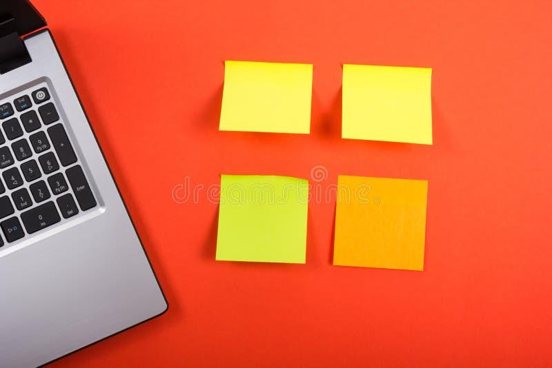 Επιτραπέζιο γραφείο γραφείων με το σύνολο ζωηρόχρωμων προμηθειών, κολλώδους σημείωσης lap-top και υπενθυμίσεων για το κόκκινο υπό στοκ φωτογραφία με δικαίωμα ελεύθερης χρήσης