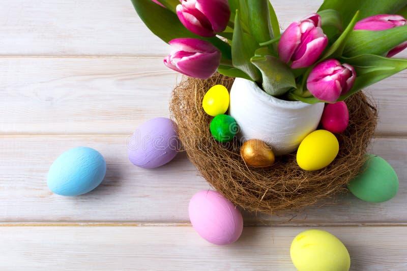 Επιτραπέζιο κεντρικό τεμάχιο Πάσχας με τα διακοσμημένα αυγά στη φωλιά και το ρόδινο TU στοκ εικόνες με δικαίωμα ελεύθερης χρήσης