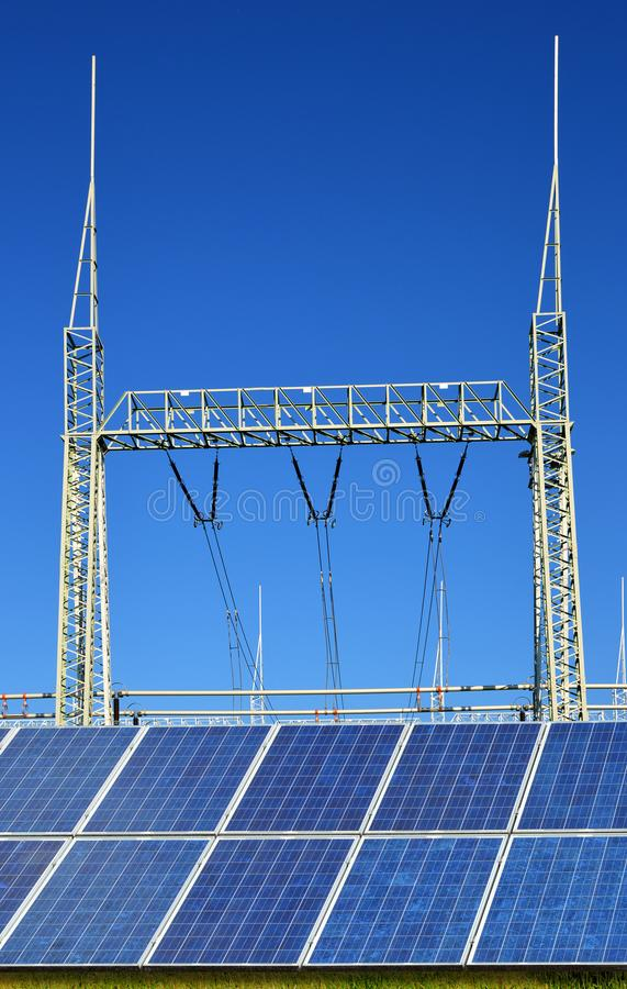 Επιτροπές ηλιακής ενέργειας στο ηλεκτρικό υποσταθμό υψηλής τάσης υποβάθρου στοκ εικόνα με δικαίωμα ελεύθερης χρήσης