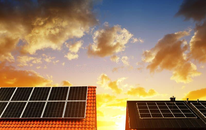 Επιτροπή ηλιακής ενέργειας στη στέγη του σπιτιού στον ουρανό ηλιοβασιλέματος υποβάθρου στοκ εικόνες