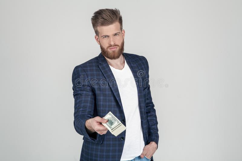 Επιτυχές άτομο με την πολύβλαστη γενειάδα πιπεροριζών Σύροντας ένα πακέτο των χρημάτων με μια κάμερα που ντύνεται σε ένα κοστούμι στοκ φωτογραφία με δικαίωμα ελεύθερης χρήσης