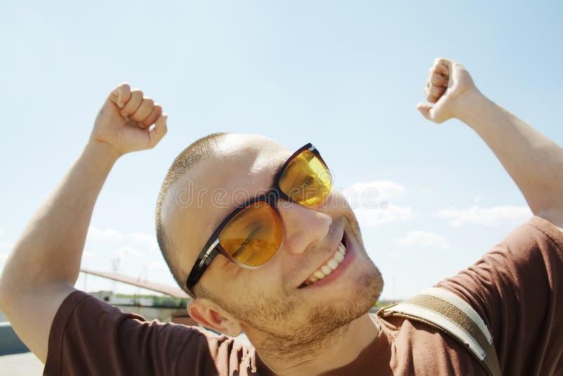 Επιτυχές άτομο στα γυαλιά ηλίου με τα όπλα επάνω στοκ φωτογραφία