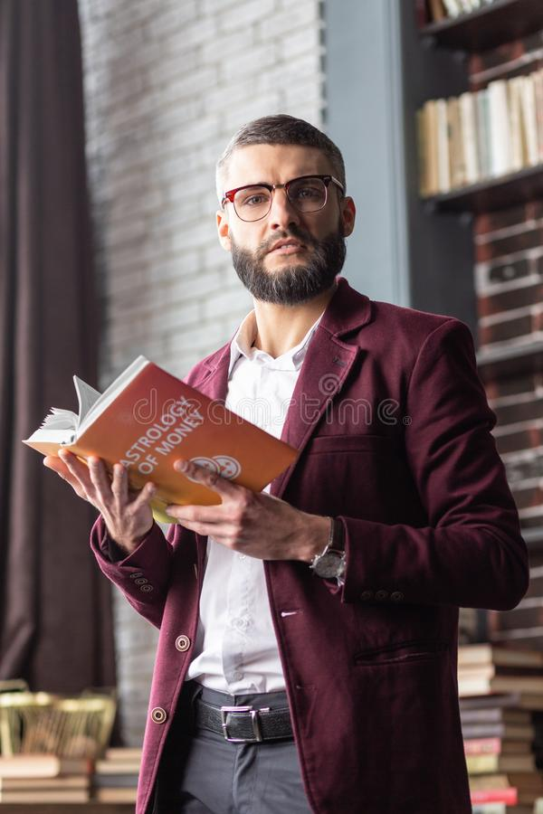 Επιτυχές βιβλίο εκμετάλλευσης επιχειρηματιών στα χέρια του που αισθάνονται περίεργα στοκ εικόνα
