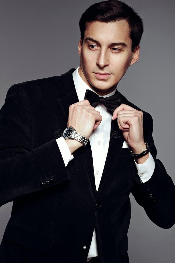 Επιτυχές επιχειρησιακό άτομο στο μαύρους κοστούμι και τον τόξο-δεσμό στοκ εικόνες