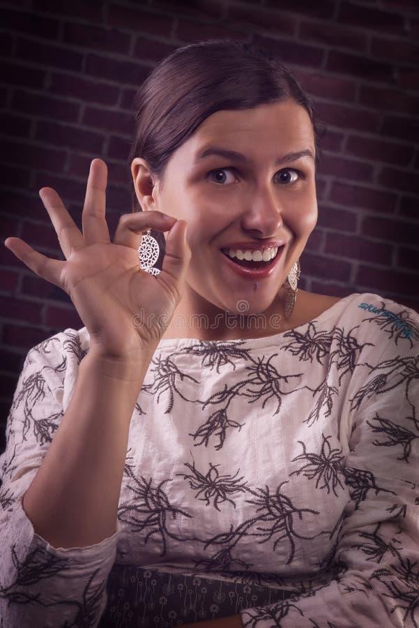 Επιτυχές ευτυχές κορίτσι που παρουσιάζει ΕΝΤΑΞΕΙ χειρονομία στοκ φωτογραφία