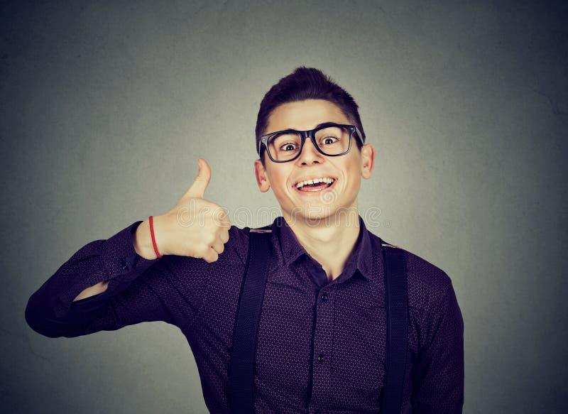 επιτυχής έφηβος Άτομο Nerdy που δίνει τους αντίχειρες επάνω στο σημάδι χειρονομίας χεριών στοκ φωτογραφία με δικαίωμα ελεύθερης χρήσης