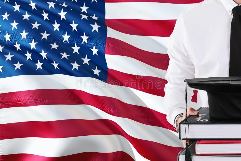 Επιτυχής αμερικανική έννοια εκπαίδευσης σπουδαστών Βιβλία και βαθμολόγηση ΚΑΠ εκμετάλλευσης πέρα από το υπόβαθρο σημαιών των Ηνωμ στοκ φωτογραφία με δικαίωμα ελεύθερης χρήσης