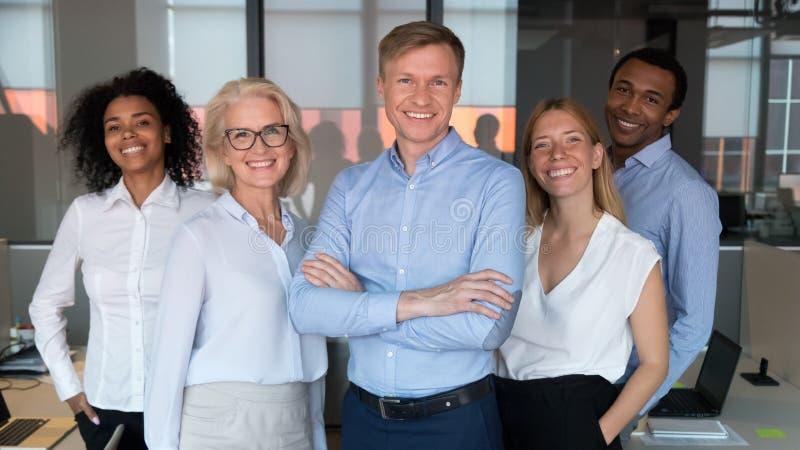 Επιτυχής αρχηγός ομάδας και διαφορετικοί υπάλληλοι που θέτουν για τη φωτογραφία από κοινού στοκ εικόνες