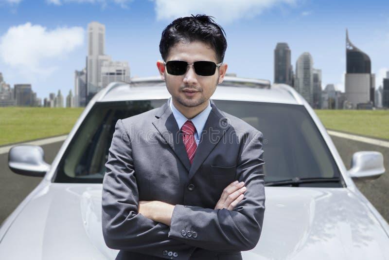 Επιτυχής ασιατικός επιχειρηματίας που φορά τα γυαλιά ηλίου μπροστά από το αυτοκίνητο πολυτέλειας στοκ φωτογραφίες