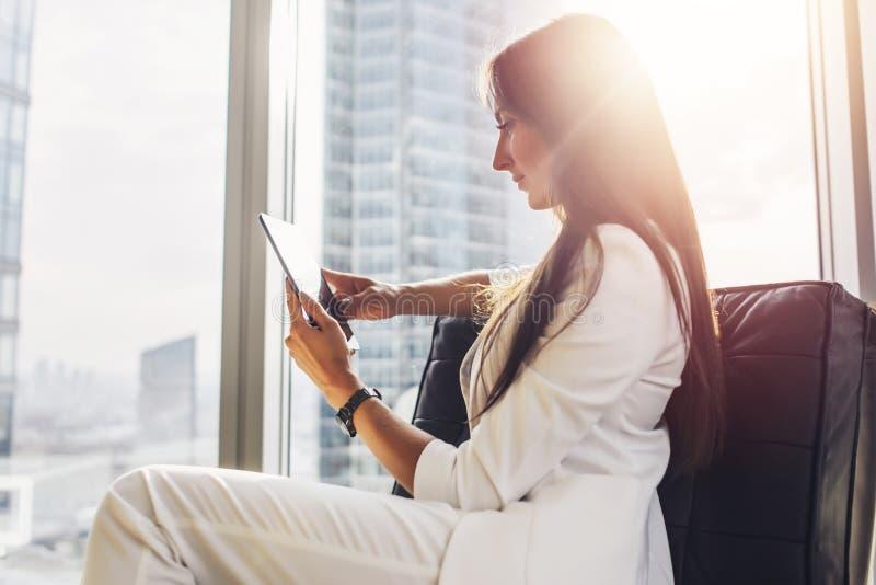 Επιτυχής γυναίκα που φορά τη συνεδρίαση κοστουμιών στην πολυθρόνα που χρησιμοποιεί τον υπολογιστή ταμπλετών στο διαμέρισμα σοφιτώ στοκ φωτογραφία