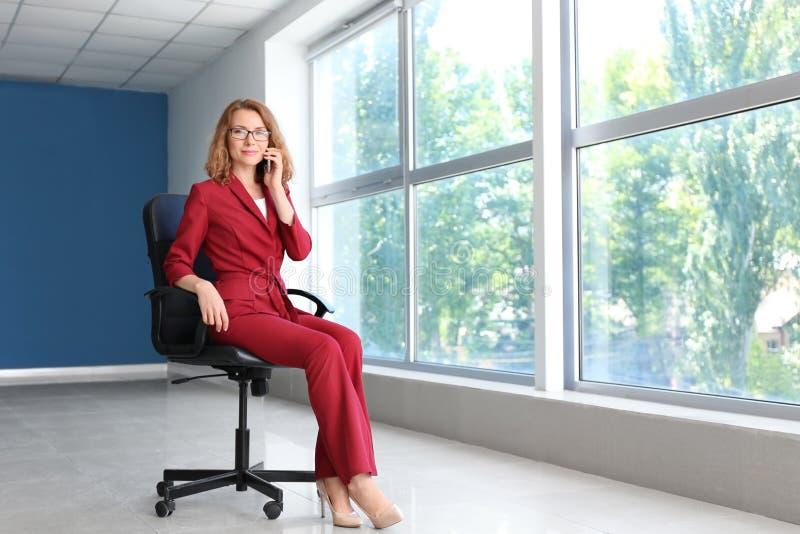 Επιτυχής επιχειρηματίας που μιλά με κινητό τηλέφωνο στο κενό γραφείο στοκ φωτογραφία