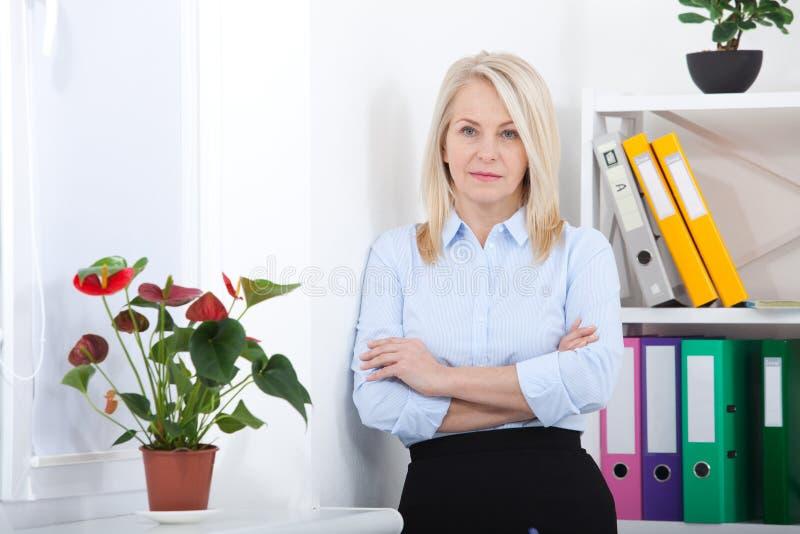 Επιτυχής επιχειρησιακή γυναίκα που φαίνεται βέβαια και που χαμογελά επιχειρησιακή γυναίκα στο μπλε πουκάμισο που φαίνεται φιλική  στοκ φωτογραφία με δικαίωμα ελεύθερης χρήσης