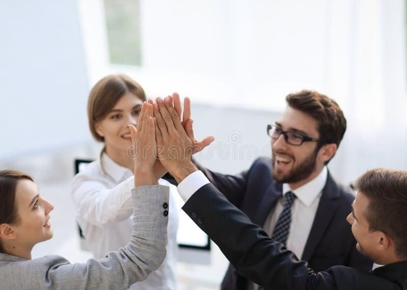 Επιτυχής επιχειρησιακή ομάδα που δίνει σε μεταξύ τους υψηλός-πέντε, στεμένος στο γραφείο στοκ εικόνα με δικαίωμα ελεύθερης χρήσης