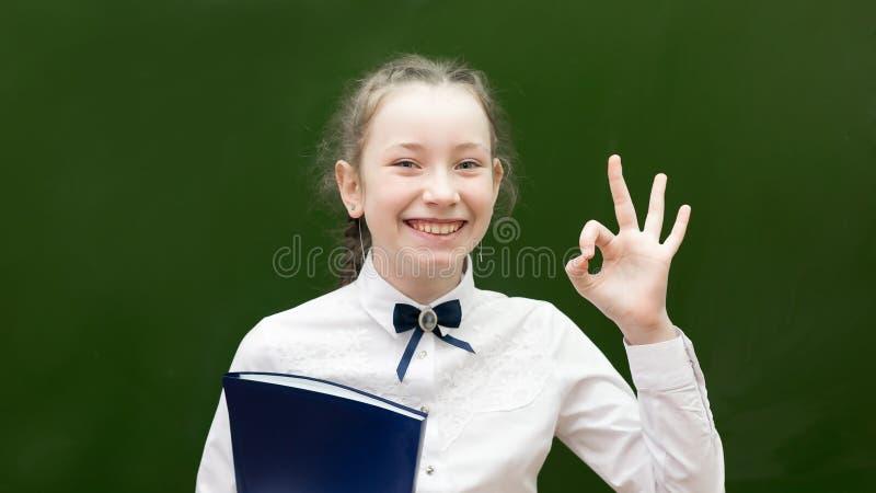 Επιτυχής μαθήτρια εφήβων που χαμογελά κρατώντας ψηλά το χέρι της στοκ φωτογραφίες με δικαίωμα ελεύθερης χρήσης