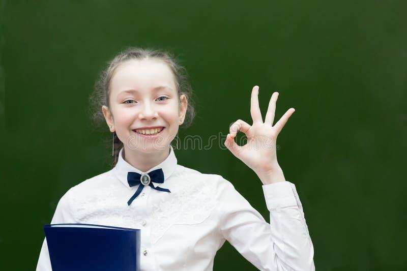 Επιτυχής μαθήτρια εφήβων που χαμογελά κρατώντας ψηλά το χέρι της στοκ εικόνα με δικαίωμα ελεύθερης χρήσης
