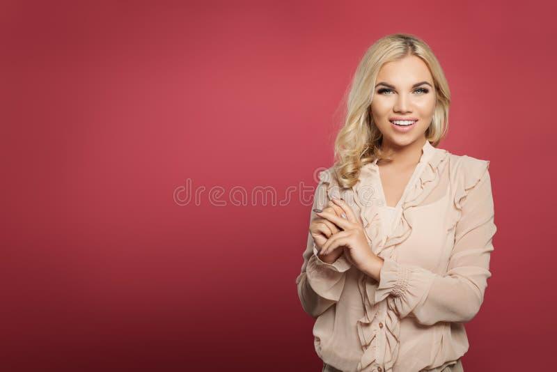 Επιτυχής νέα γυναίκα που στέκεται στο ρόδινο κλίμα τοίχων ξανθό χαμόγελο κοριτσιών στοκ εικόνες