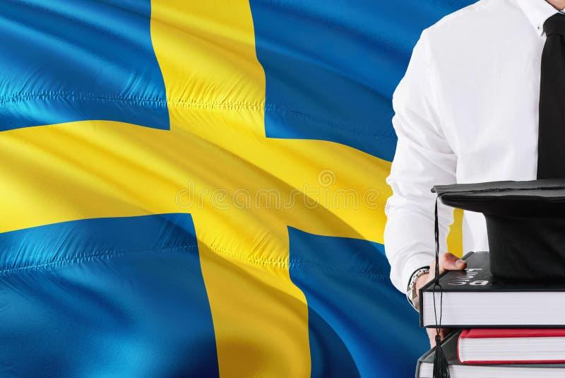 Επιτυχής σουηδική έννοια εκπαίδευσης σπουδαστών Βιβλία και βαθμολόγηση ΚΑΠ εκμετάλλευσης πέρα από το υπόβαθρο σημαιών της Σουηδία στοκ εικόνες