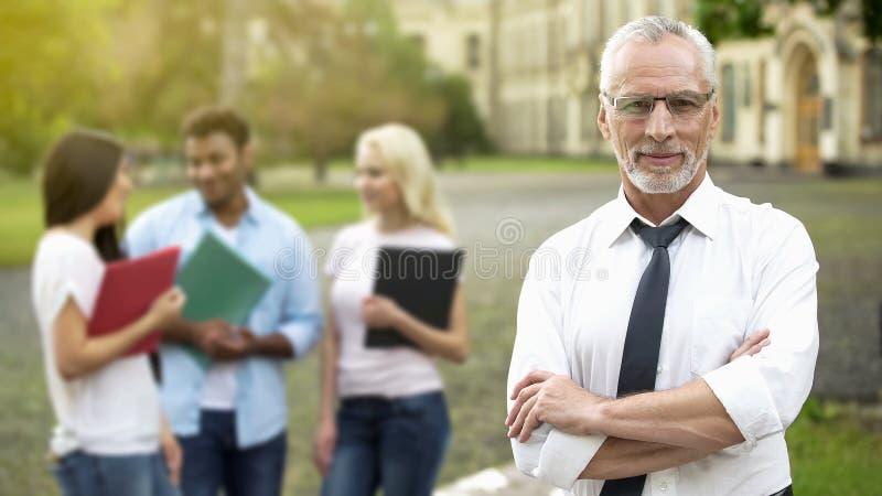 Επιτυχής τοποθέτηση καθηγητή με τα χέρια που διασχίζονται, πανεπιστημιακή εκπαίδευση, μέλλον στοκ φωτογραφία με δικαίωμα ελεύθερης χρήσης