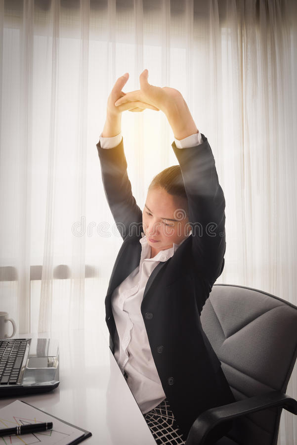 Επιτυχής χαλάρωση επιχειρηματιών στην καρέκλα της στο γραφείο στοκ εικόνες