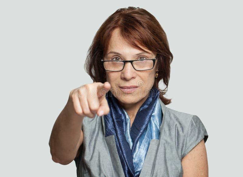 Επιτυχής ώριμη γυναίκα επιχειρηματιών που δείχνει στη κάμερα στοκ φωτογραφίες