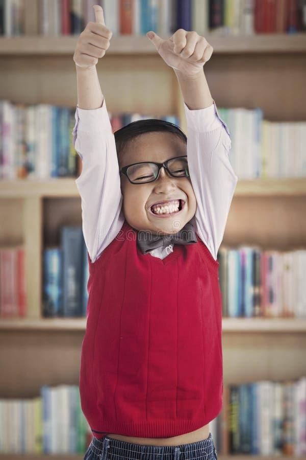 Επιτυχής schoolboy στη βιβλιοθήκη στοκ εικόνες