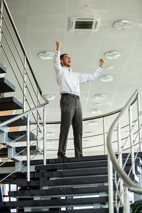 επιτυχία εορτασμού Η συγκινημένη νέα κράτηση επιχειρηματιών οπλίζει αυξημένος και εκφράζοντας τη θετική σκέψη στεμένος στην αρχή στοκ φωτογραφία με δικαίωμα ελεύθερης χρήσης