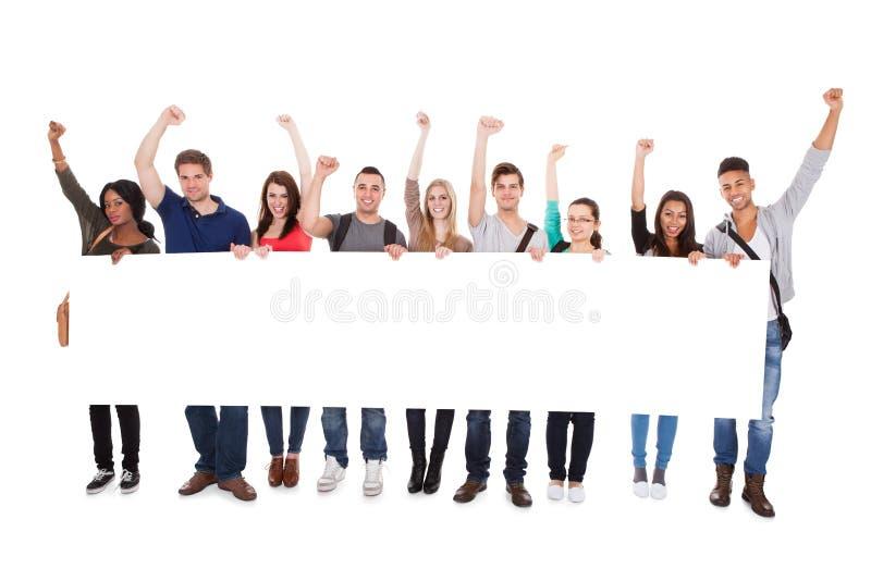 Επιτυχείς φοιτητές πανεπιστημίου που επιδεικνύουν τον κενό πίνακα διαφημίσεων στοκ φωτογραφία με δικαίωμα ελεύθερης χρήσης