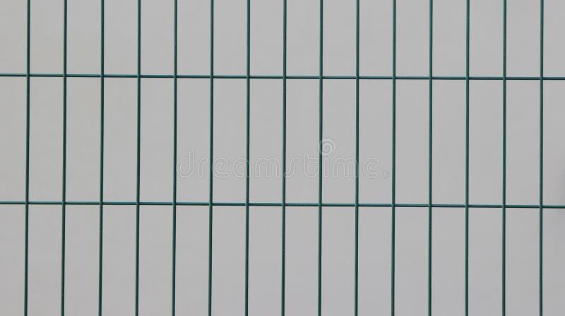 Επιφάνεια ενός ενωμένου στενά φράκτη καλωδίων με τα ορθογώνια στοιχεία που χρωματίζονται σε πράσινο μπροστά από έναν άσπρο τοίχο στοκ εικόνες με δικαίωμα ελεύθερης χρήσης