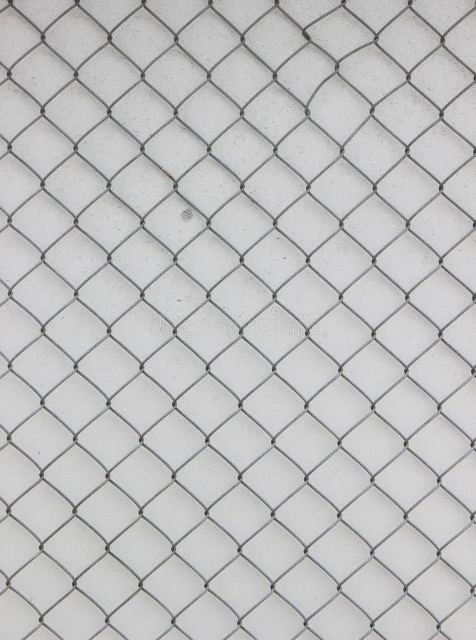 Επιφάνεια μιας αλιείας με δίχτυα καλωδίων με τα diamond-shaped στοιχεία μπροστά από έναν άσπρο τοίχο στοκ εικόνες