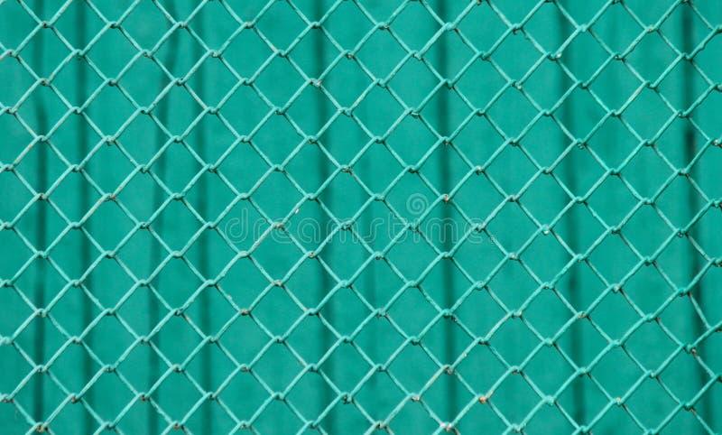 Επιφάνεια μιας αλιείας με δίχτυα καλωδίων με τα diamond-shaped στοιχεία που χρωματίζονται σε πράσινο μπροστά από έναν πράσινο τοί στοκ εικόνα με δικαίωμα ελεύθερης χρήσης