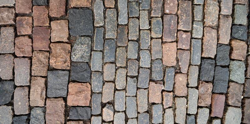 Επιφάνεια των παλαιών ζωηρόχρωμων τετραγωνικών πετρών επίστρωσης στοκ φωτογραφία με δικαίωμα ελεύθερης χρήσης