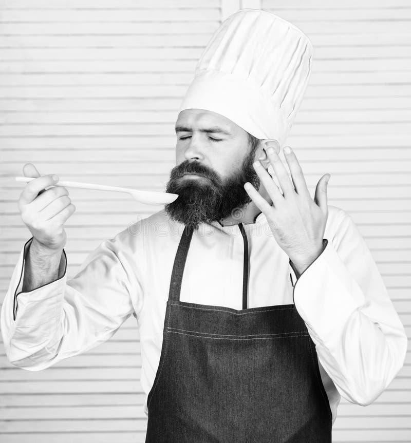 Επιχείρηση Γενειοφόρος μάγειρας ατόμων στην κουζίνα, μαγειρική o Άτομο αρχιμαγείρων στο καπέλο Μυστικό γούστο στοκ φωτογραφία