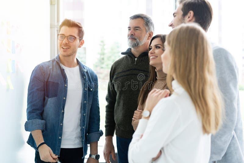 Επιχείρηση, εκπαίδευση και έννοια γραφείων - επιχειρησιακή ομάδα με τον πίνακα κτυπήματος στην αρχή συζητώντας κάτι στοκ εικόνα